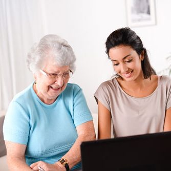 JFS Care. An elderly woman is helped learning to use a computer.